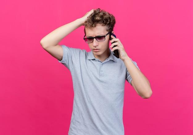 Giovane deluso con gli occhiali neri che indossa una polo grigia che tocca la sua testa essendo confuso mentre parla al telefono cellulare in piedi sopra il muro rosa