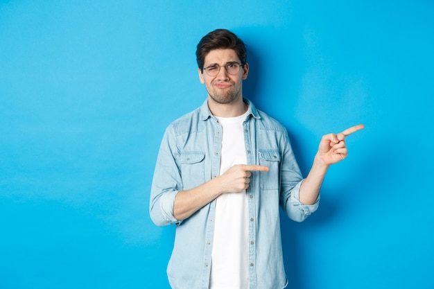 Disappointed young man in glasses pointing fingers right at copy space, showing promo banner and smirking dissatisfied, judging bad product, standing over blue background.