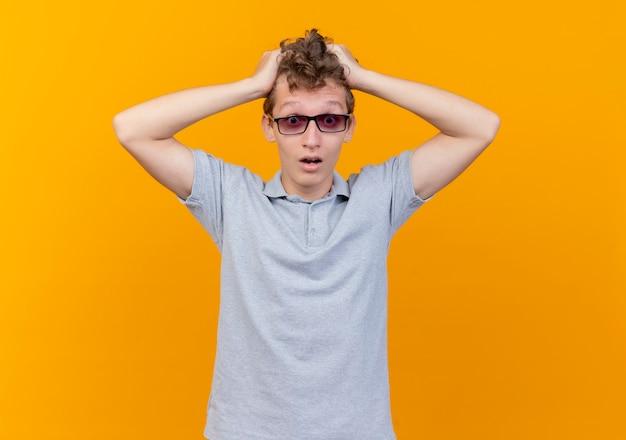 Разочарованный молодой человек в черных очках, одетый в серую рубашку-поло, касается его головы, смущенный оранжевым