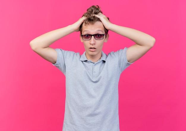 Разочарованный молодой человек в черных очках, одетый в серую рубашку поло, касается его головы, смущенный, стоя у розовой стены