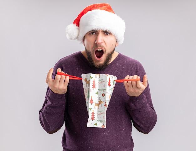 보라색 스웨터와 산타 모자 오프닝 선물 종이 봉지에 실망 된 젊은 남자가 흰색 배경 위에 서있는 공격적인 표정으로 소리