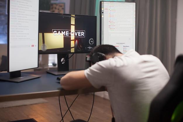 Разочарованный молодой человек держит голову в офисе, потому что для него игра в онлайн-стрелялки окончена.