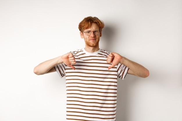 赤い髪と眼鏡をかけた失望した若い男は反対し、白い背景の上に立って、親指を下に向けて眉をひそめている。