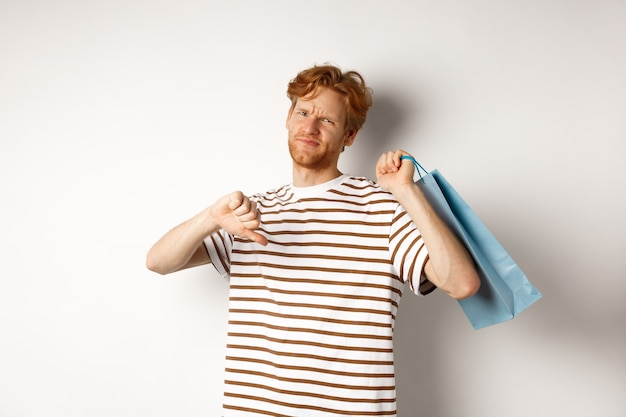 Disappointed young man with red hair and beard showing thumbs-down after bad shopping experience, holding bag over shoulder and frowning upset, white background.