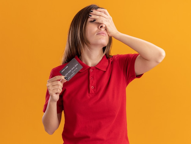 Disappointed young pretty caucasian girl puts hand on face and holds credit card on orange