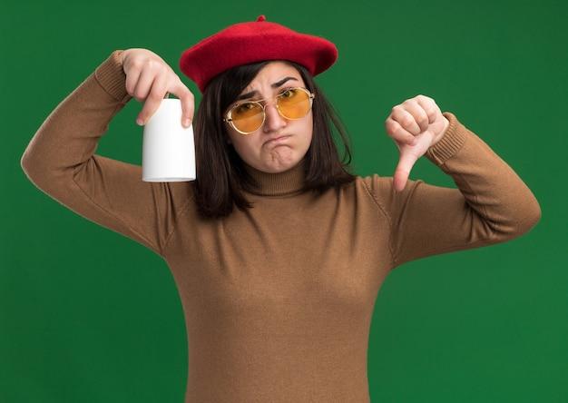컵을 거꾸로 들고 녹색에 아래로 푼다 태양 안경에 베레모 모자와 실망 된 젊은 예쁜 백인 여자