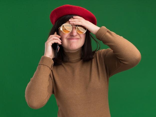 태양 안경에 베레모 모자와 실망 된 젊은 예쁜 백인 여자 전화 회담과 녹색 이마에 손을 넣습니다