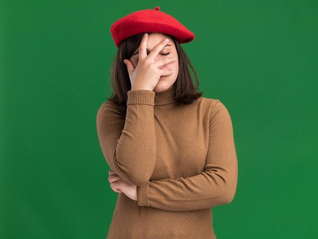 Разочарованная молодая симпатичная кавказская девушка в берете кладет руку на лицо на зеленом