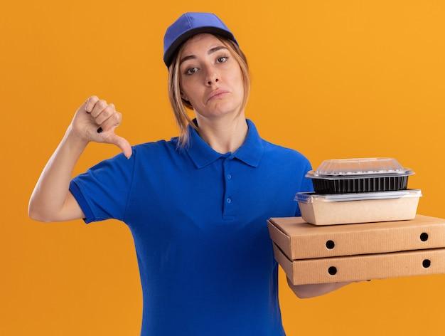 Разочарованная молодая симпатичная доставщица в униформе показывает большие пальцы руки вниз и держит бумажные пакеты с едой