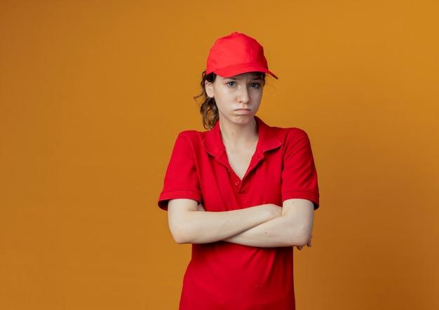 Giovane ragazza graziosa di consegna delusa in uniforme rossa e cappuccio che stanno con la posizione chiusa isolata su fondo arancio con lo spazio della copia