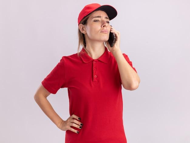 Giovane donna graziosa di consegna delusa in colloqui uniformi sul telefono e guarda al lato isolato sul muro bianco