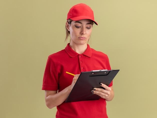 La giovane donna graziosa di consegna delusa in uniforme scrive negli appunti con la penna isolata sulla parete verde oliva