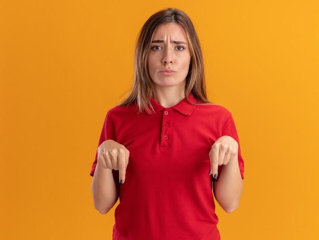 Разочарованная молодая красивая женщина показывает палец вниз двумя руками, изолированными на оранжевой стене