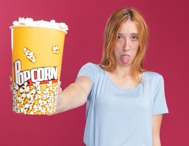 Una giovane ragazza rossa e rossa delusa con le lentiggini tira fuori la lingua e tiene un secchio di popcorn