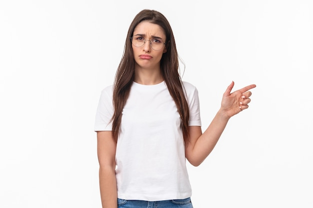 Disappointed young silly complaining girl in glasses