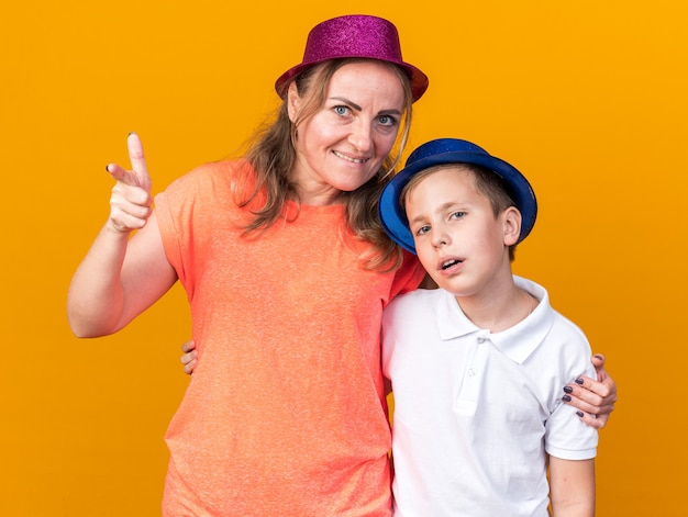 Disappointed young slavic boy with blue party hat standing with his mother wearing purple party hat and pointing at side isolated on orange wall with copy space