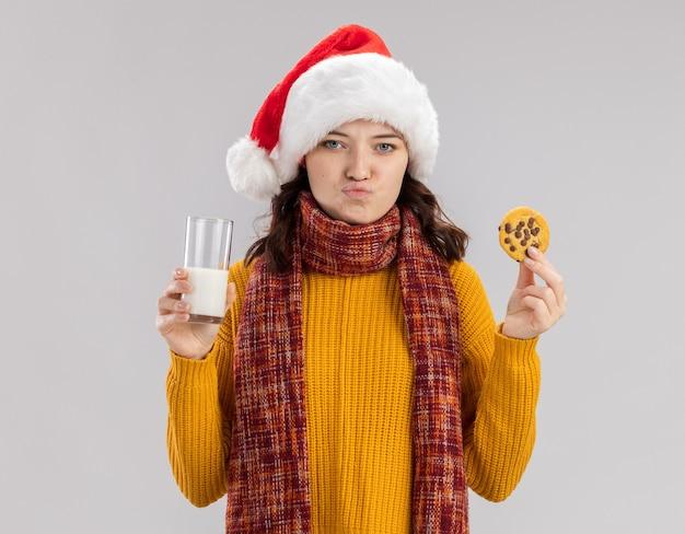 산타 모자와 목에 스카프와 우유와 비스킷 복사 공간이 흰 벽에 고립 된 유리를 들고 실망 된 젊은 슬라브 소녀