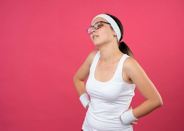 ヘッドバンドを身に着けている光学メガネで失望した若いスポーティな女の子