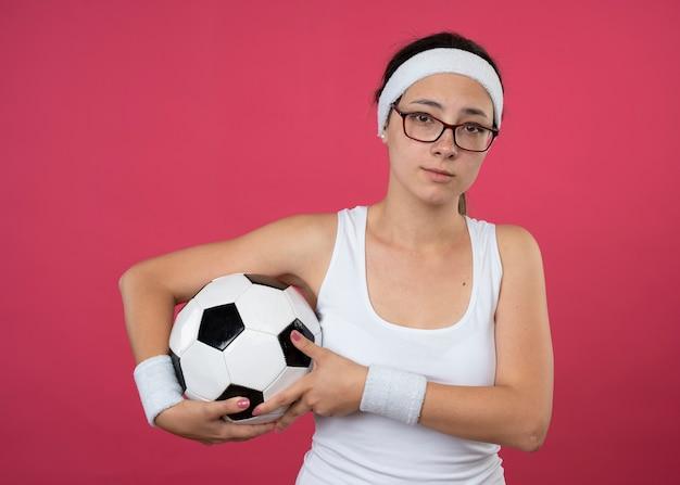 La giovane donna sportiva delusa in vetri ottici che indossa la fascia e i braccialetti tiene la sfera isolata sulla parete rosa