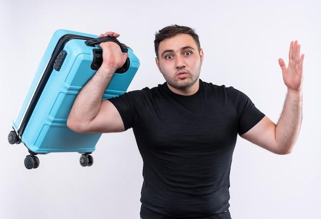 Разочарованный молодой путешественник в черной футболке держит чемодан, поднимающий руку, стоящую над белой стеной