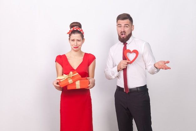 Disappointment. woman holding gift box and cry, man confused. indoor, studio shot, isolated on gray background