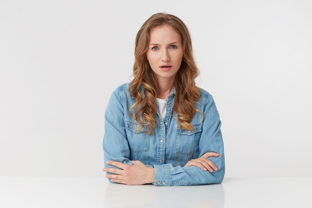 テーブルに座って、長いブロンドのウェーブのかかった髪をして、デニムシャツを着ている不承認の若い女性は、悪い知らせを聞いた。白い背景の上に分離されたカメラを見てください。