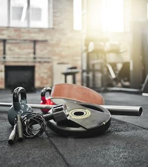 分解されたバーベル、薬のボール、ケトルベル、ダンベル、ジムの床に横たわっている縄跳び。フリーウェイトでトレーニングするためのスポーツ用品。ファンクショナルトレーニング