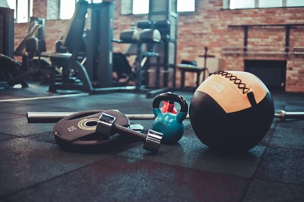 Disassembled barbell, medicine ball, kettlebell, dumbbell lying on floor in gym.