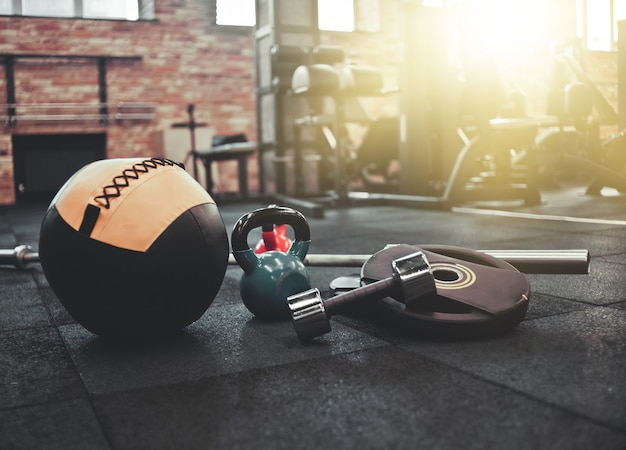 分解されたバーベル、薬のボール、ケトルベル、ジムの床に横たわっているダンベル。フリーウェイトでトレーニングするためのスポーツ用品。ファンクショナルトレーニング