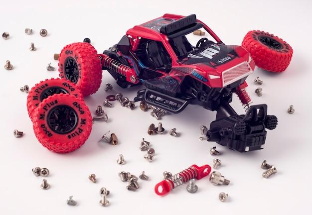 分解された車と散らばった部品。白い背景で隔離の壊れたおもちゃ