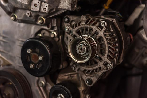 ガレージで解体車の汚れたエンジンとダイナモ