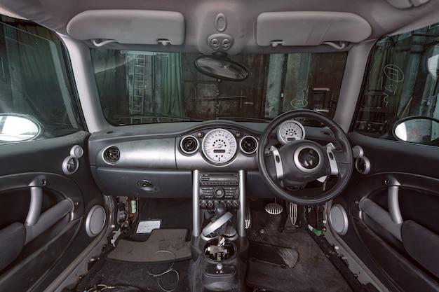ドアが付いている分解された車のインテリア。車のワークショップの肘掛け椅子および他のパネル。オートサービスで働く