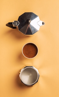 Disassembled geyser coffee maker on light brown paper coffee preparation concept