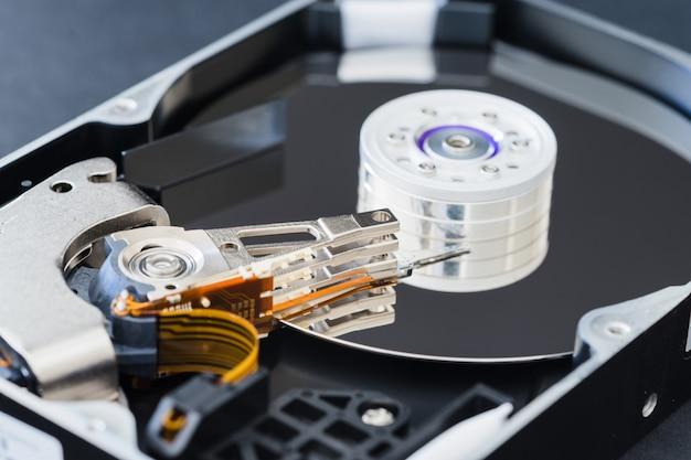 Разобранный жесткий диск внутри крупным планом, шпиндель, рычаг привода, считывающая головка записи, диск