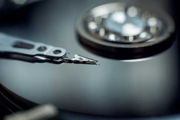Disassembled hard disk. read head, magnetic disk and spindle close-up.