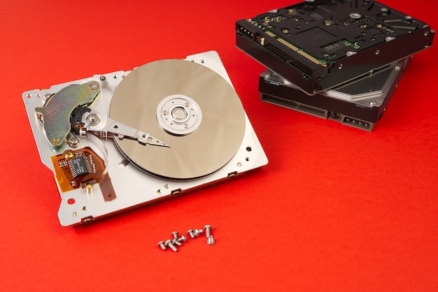 Disassembled hard drive from the computer on red