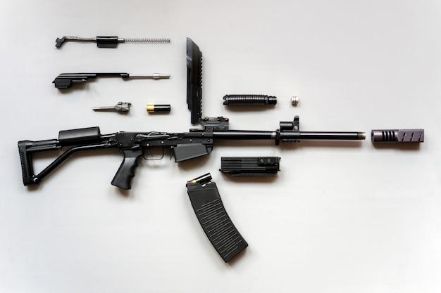 灰色の背景に分解された機関銃。孤立。分解された状態の銃の詳細。