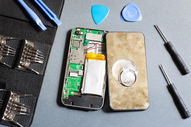 수리 도구가있는 분해 된 휴대폰