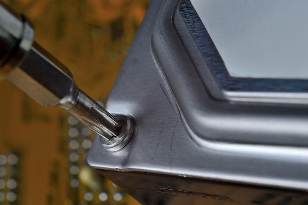 Разборка жесткого диска компьютера с помощью отвертки для диагностики и устранения проблем.