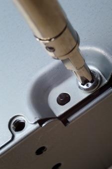 작은 드라이버로 금속 컴퓨터 케이스를 분해합니다. 확대