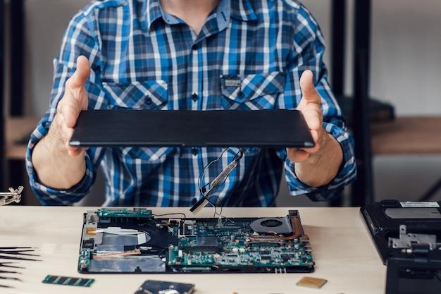修理工場で人がコンピューターを分解する