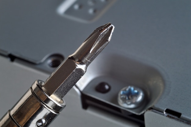 Disassembling a metal computer case with a small screwdriver