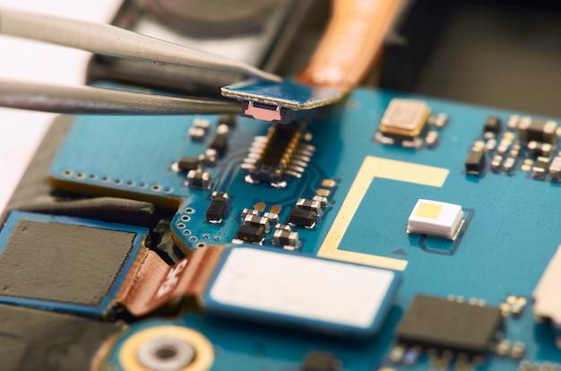 電気ボードを内側に見せるスマートフォンの分解。電話は固定しています
