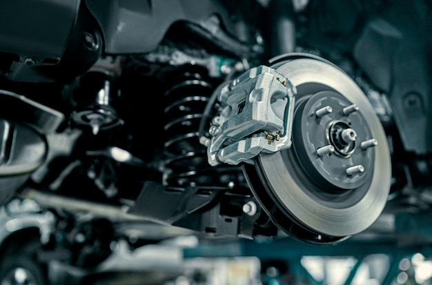 Дисковый тормоз автомобиля в ремонте, при замене шины на новую. ремонт автомобильных тормозов в гараже. подвеска автомобиля для обслуживания тормозов и систем амортизаторов. крупным планом.