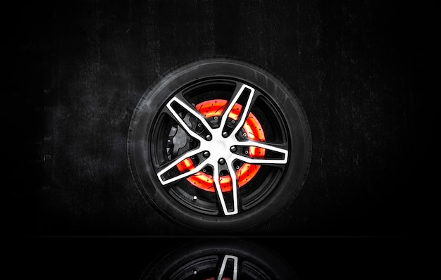 Disc brake scratch burning in a racing wheel on black cement wall background.