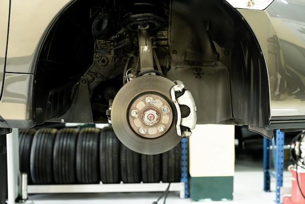 Дисковый автомобиль крупным планом - механик отвинчивает автомобильные детали во время работы под поднятым автомобилем - концепция автосервиса