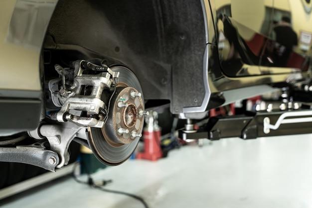 ディスクカーのクローズアップ-持ち上げられた自動車の下で作業している間に整備士が自動車部品のネジを緩める-カーサービスの概念