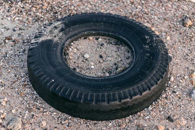 Discarded tire lying on the beach, environmental contamination
