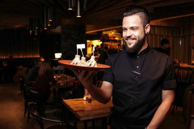 A discerning waiter in black clothes, with a beard and a portion of khinkali