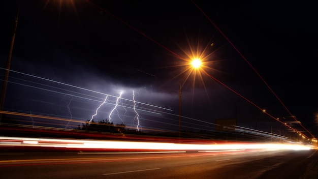 Discharges of lightning in the night sky over the road background